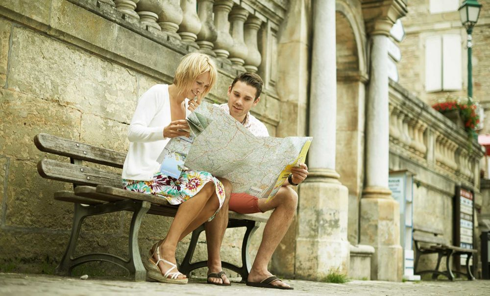lifestyle photography of a couple lost and looking at a map in france