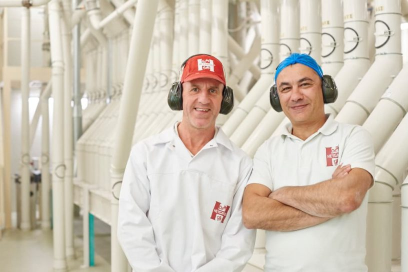 2 men posing for camera infront of Grain machine in bakery