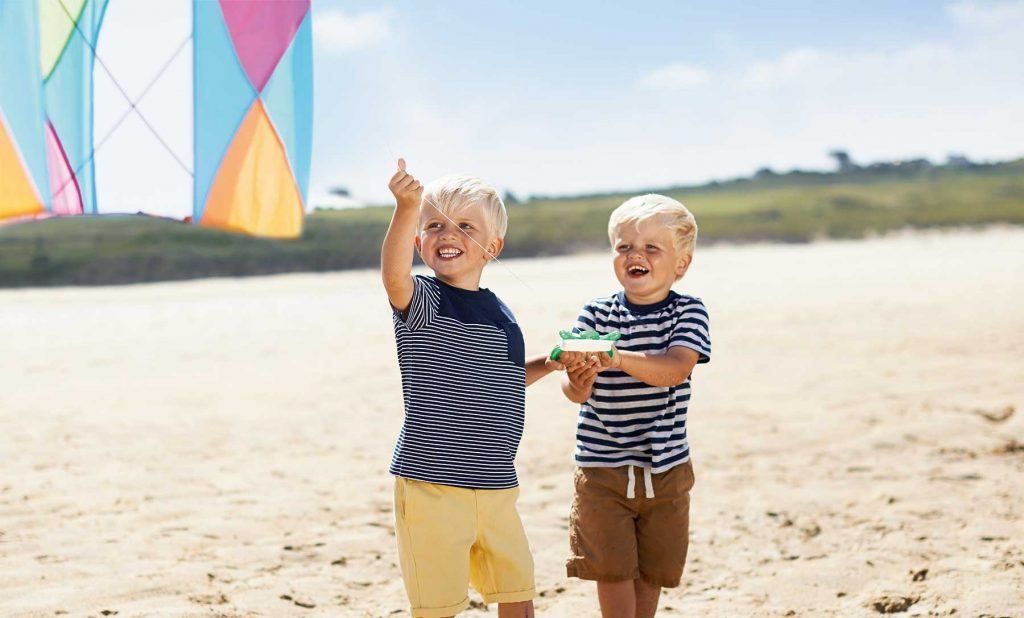 lifestyle photography of boys on a beach playing with a kite