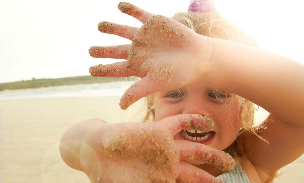 Lifestyle-photography of girl on beach playing with sandy hands