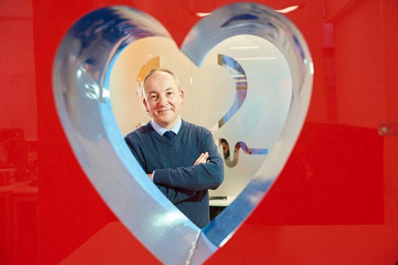 man standing behind heart shaped hole in plastic wall smiling to camera